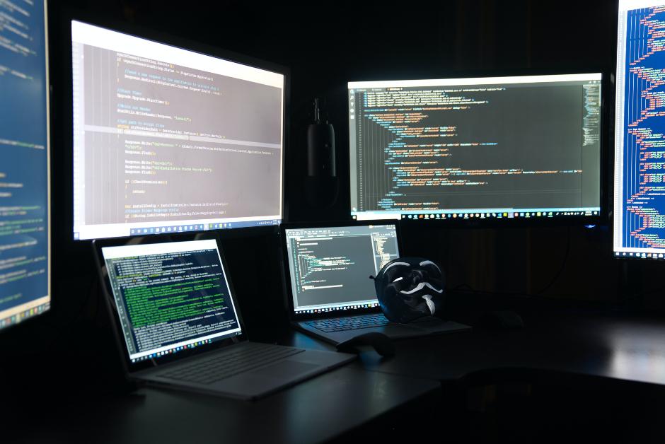 Postazione lavoro con molti computer e codici HTML